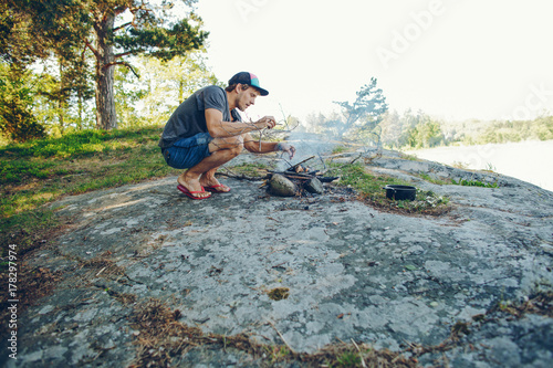 Young man on the beach making a bonfire on a large rock