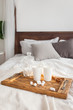 Two mugs on a tray white bed with a cinnamon stick, breakfast concept