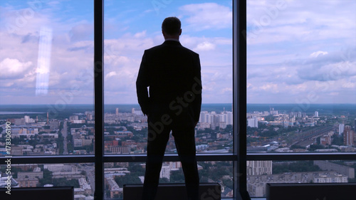 Businessman standing near the window and looking into it. Man stands near the stained glass