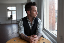 Tattooed Man Wearing Paisley Shirt And Black Vest Staring Out Window