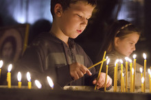 Boy And Girl Lighting Candles In Church
