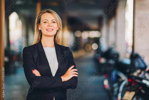 Fotografia  Portrait of beautiful blond woman on the street, wearing black jacket, arms cros