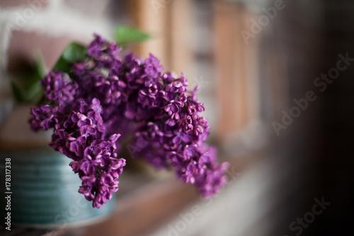 blue potter vase filled with purple lilacs sitting on wooden ledge