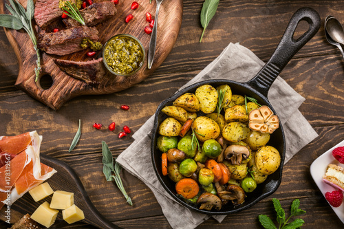 Spoed Fotobehang Klaar gerecht Fried potatoes with vegetables and herbs on wooden background. Healthy food concept. Overhead shot.