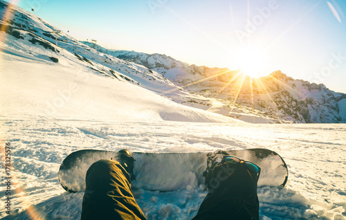 obraz dibond Snowboarder sitting at sunset on relax moment in french alps ski resort - Winter sport concept with adventure guy on top of mountain ready to ride down - Legs view point with teal and orange filter