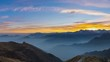 Panorama on the Alps at sunset. Stunning colorful sky, high altitude mountain peaks, fog in the valleys.