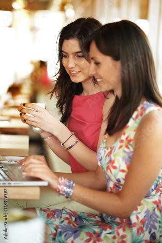 Plakat Dwie dziewczyny siedzą w kawiarni i za pomocą laptopa