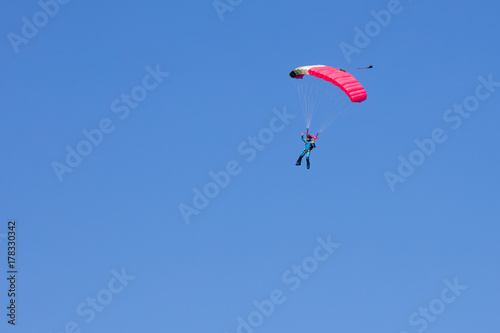 Foto op Canvas Luchtsport skydiver on black and pink parachute in summer day