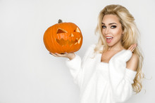 Beautiful Young Woman In White Sweater, Standing On White Background And Holding Pumpkin;