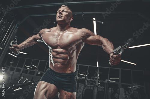 Vászonkép  Brutal Caucasian bodybuilder training chest in gym