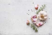 Garlic. Garlic Bulbs. Fresh Garlic With Rosemary And Pepper On White Concrete Board