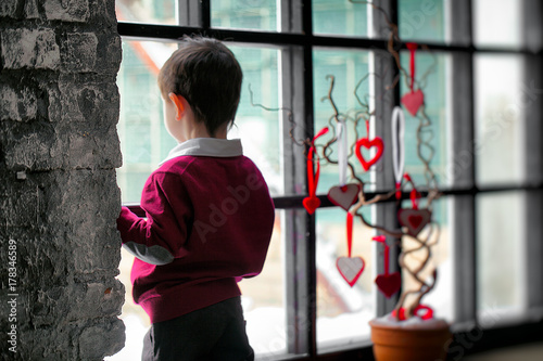Fotografie, Obraz  A boy is looking out of the window waiting for something or somebody near a composition with red hearts