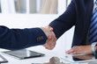 Business handshake at meeting or negotiation in the office. Partners are satisfied because signing contract or financial papers