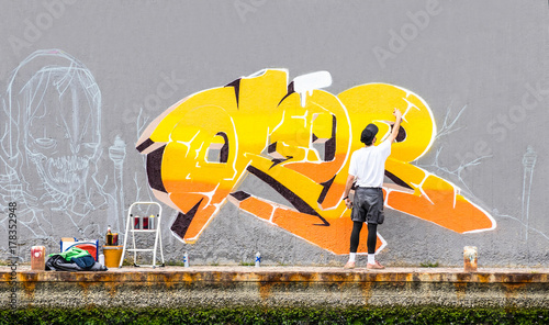 plakat Street artist painting colored graffiti on public space wall - Modern art concept of urban guy performing and preparing live murales paint with yellow aerosol color spray - Cloudy afternoon filter