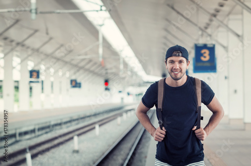 Young traveler walking with backpack on train station