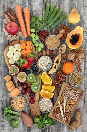 Fototapeta Health food concept for a high fibre diet with fruit, vegetables, cereals, nuts, seeds, whole wheat pasta, grains, legumes and spice. Foods high in omega 3, anthocyanins and antioxidants,  top view. obraz