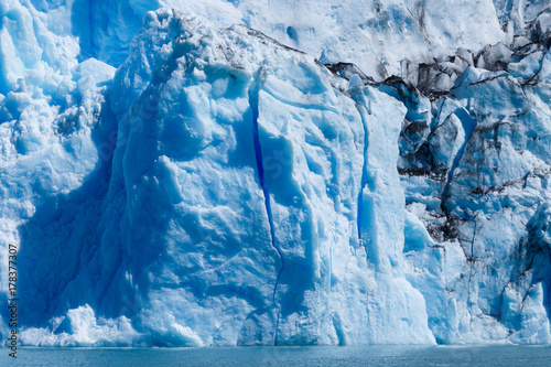 Plakat Język Glaciar Spegazzini odbijający niebieskie i purpurowe światło w głębokich pęknięciach w lodzie