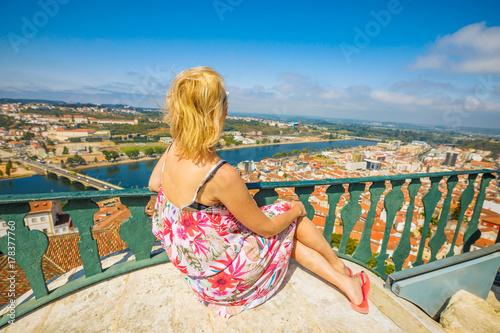 In de dag Havana Coimbra cityscape and Santa Clara Bridge on Mondego river. Caucasian tourist woman admiring Coimbra panorama sitting on top of bell Clock Tower. Female tourist enjoys in Portugal, Europe.