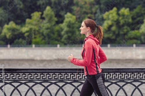 Zdjęcie XXL młoda dziewczyna fitness działa w parku