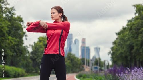 Zdjęcie XXL młody biegacz dziewczyna fitness rozciąga ramiona przed uruchomieniem w mieście