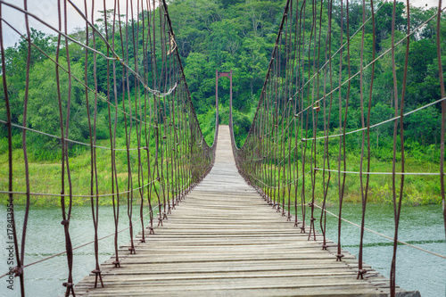 In a long suspension wooden bridge over natural lake. It is at Kaeng Krachan Reservoir National Park in Phetchaburi, Thailand, Southeast Asia.