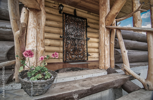 Fotografie, Obraz  porch with door of wooden rural house with flowers on its steps