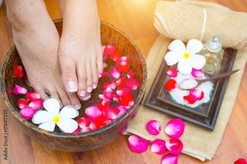 Poster Pedicure Closeup photo of a female feet at spa salon on pedicure procedure. Female legs in water decoration the flowers.