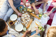 Various food on picnic table and several friends around it eating sandwiches and fruit and drinking homemade lemonade