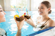 Happy girls with exotic cocktails toasting while relaxing in water of swimming-pool