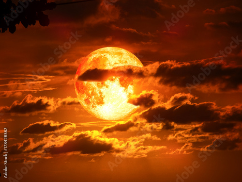 super moon on silhouette cloud in red sky