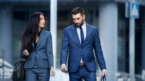 Fotografia  Business Woman and Business Man in Tailored Suits Walk on the Busy Big City Street