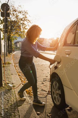 Zdjęcie XXL Młoda kobieta ładuje elektryczny samochód. Wypożyczany samochód ładuje się w stacji ładowania pojazdów elektrycznych. Dzielenie samochodów.
