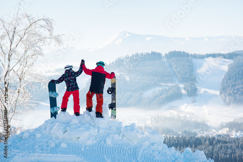 Couple snowboarders high fiving each other, standing on top of a snowy mountain, observing stunning winter view, resting after snowboarding at ski resort on a beautiful sunny winter day, Bukovel
