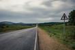 Asphalt road to the horizon line under a cloudy sky.