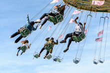 A Rotating Chair Swing Ride Carousel With Teenagers Enjoying The Ride In A Parisian Amusement Park.