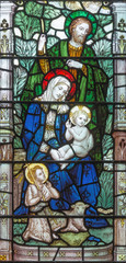 Fototapeta Witraże sakralne LONDON, GREAT BRITAIN - SEPTEMBER 17, 2017: The Holy Family on the stained glass in church Holy Trinity Brompton.