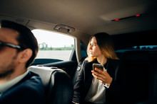 Business Woman Using Smart Phone And Smiling While Sitting On Back Seat In Car