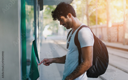 Obraz Bearded handsome hipster guy wearing casual clothes with backpack is buying bus tickets at self service vending machine on the station during vacation trip to European city. Flare light. - fototapety do salonu