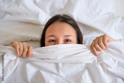 Plakat Kobieta otwiera oczy kłama na łóżku