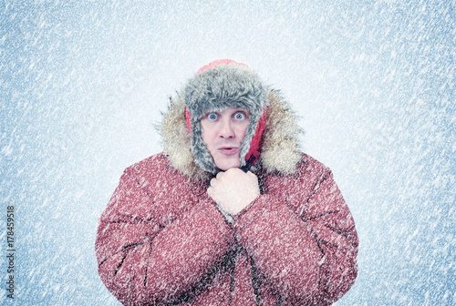 Obraz Frozen man in winter clothes warming hands, cold, snow, blizzard - fototapety do salonu