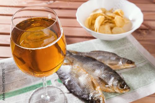 Plakat Piwo jasne i suche ryby, czosnek i frytki na drewnianym stole