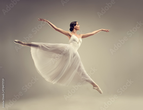 plakat Ballerina. Young graceful woman ballet dancer, dressed in professional outfit, shoes and white weightless skirt is demonstrating dancing skill. Beauty of classic ballet.
