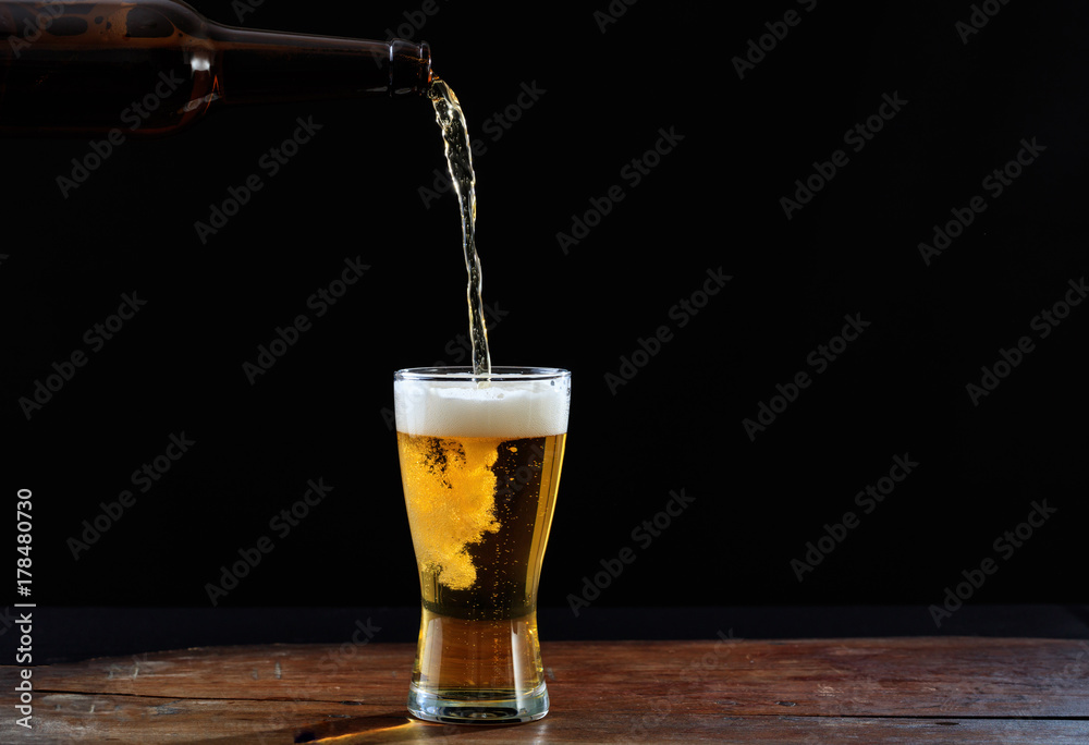 Fototapety, obrazy: Pouring beer in a glass on a wooden table, dark background