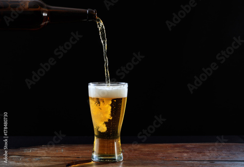 Stampa su Tela  Pouring beer in a glass on a wooden table, dark background