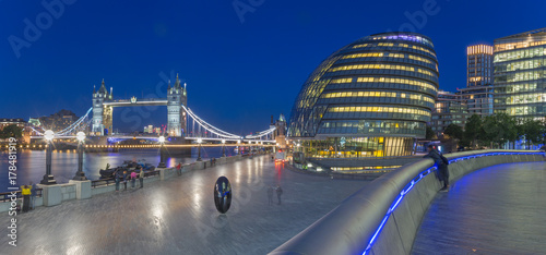 Photo  London - The panorama of the Tower bridge, promenade with the the modern Town Hall building at dusk