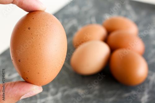 Plakat trzymać jajko palcem i rozmycie tła jaj kurzych
