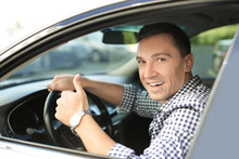 Happy Man Sitting In Car And Showing Thumb Up