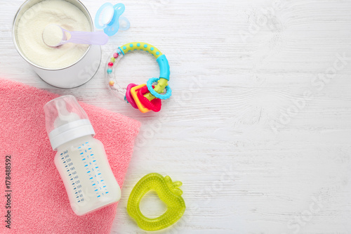 Composition with feeding bottle of baby milk formula on wooden table