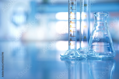 glass flask with cylinder in blue science laboratory background