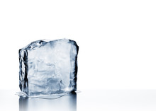 Cold Blue Crystal Clear Frozen Block Of Ice Melting To Create Pool Of Water On Reflective Steel Surface